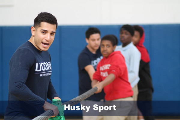 phd student, michael corral playing tug of war with students in hartford